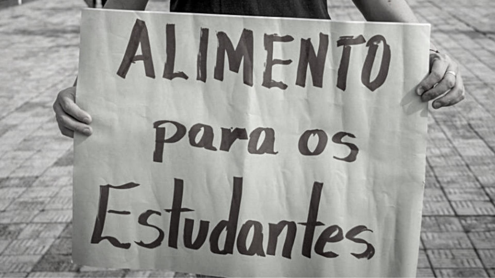 """Foto tem pessoa segurando cartaz onde se vê texto """"Alimento para os estudantes"""""""